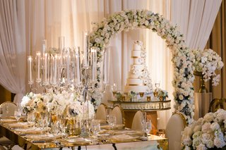 wedding-cake-sugar-flowers-under-flower-arch-long-table-candelabra-gold-chairs-white-flowers