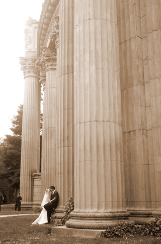 sepia-toned-photo-of-bride-and-groom-by-large-building