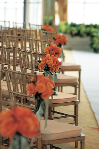 ceremony-chairs-decorated-with-orange-rose-bouquets-and-green-ribbon
