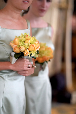 bridesmaids-hold-small-bouquets-of-orange-and-green-flowers