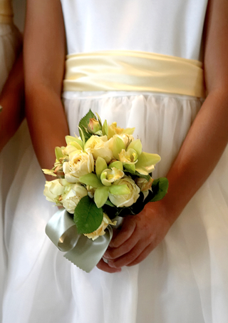 flower-girl-holds-bouquet-of-orchid-and-rose-flowers