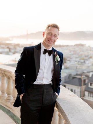 groom-on-balcony-in-navy-velvet-jacket-black-lapels-black-trousers-bow-tie