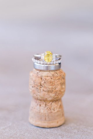 yellow-diamond-oval-engagement-ring-and-eternity-band-on-top-of-champagne-cork