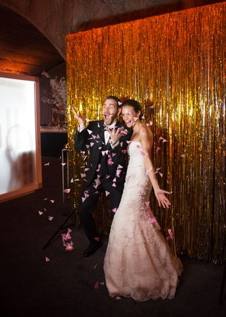 newlyweds-strike-a-silly-and-playful-pose-for-their-photo-booth-and-throw-pink-flower-petals
