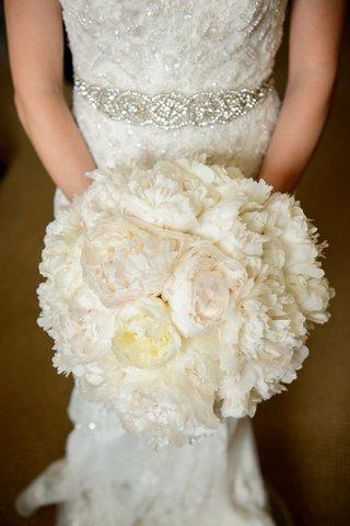 bride-in-beaded-wedding-dress-crystal-belt-sash-holding-white-ivory-bouquet-of-peony-flowers