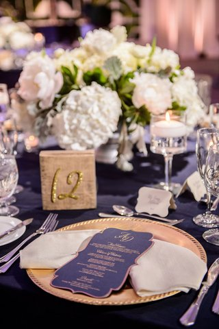 wedding-reception-navy-linen-low-centerpiece-white-hydrangea-peony-rose-table-number-gold-and-menu