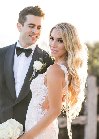 groom-smiles-at-bride-long-blonde-hair-with-pearls-draping-along-low-back-lace-galia-lahav-open-back