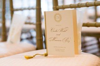 wedding-ceremony-program-white-stationery-gold-lettering-monogram-tie-tassel-on-chair