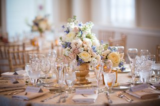 table-decorated-with-short-gold-vase-and-pink-white-and-blue-flowers