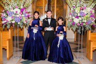 wedding-at-church-purple-flower-arrangements-flower-girls-in-royal-blue-ball-gowns-ring-bearer
