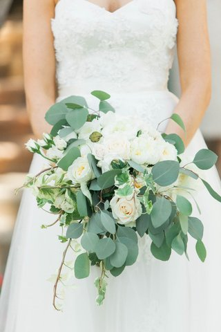 bride-holding-wedding-bouquet-with-white-roses-eucalyptus-leaves-and-ivy