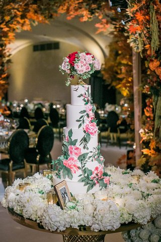 5-tier-wedding-cake-with-pink-flower-and-greenery-on-bed-of-white-flowers