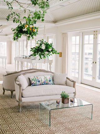 wedding-reception-hanging-flower-arrangements-from-ceiling-antique-settee-with-watercolor-pillow