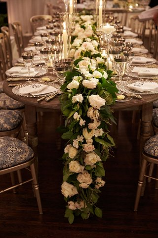 head-table-with-wood-table-patterned-seat-cushions-garland-of-white-roses-green-leaves-candles