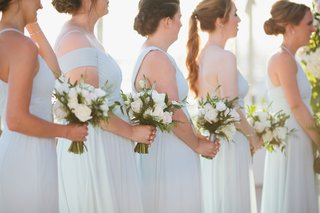 bridesmaids-with-low-buns-ivory-flower-bouquets-sunset-ocean-view-ceremony