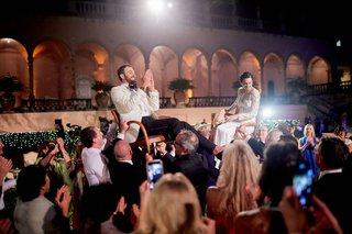 ringling-museum-wedding-reception-outdoors-bride-and-groom-lifted-in-hora