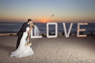 bride-in-strapless-wedding-dress-dipped-by-groom-in-tuxedo-kissing-at-sunset-on-beach-in-mexico