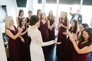 bride-in-white-wedding-dress-long-sleeve-showing-bridesmaids-her-dress-bridesmaid-burgundy-gowns