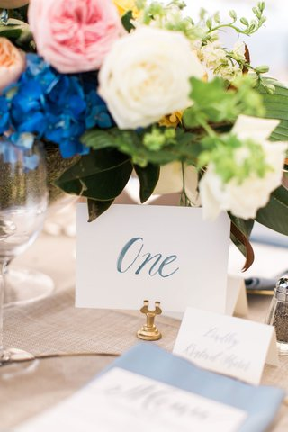 wedding-reception-gold-stand-card-holder-table-number-with-blue-calligraphy-under-low-centerpiece