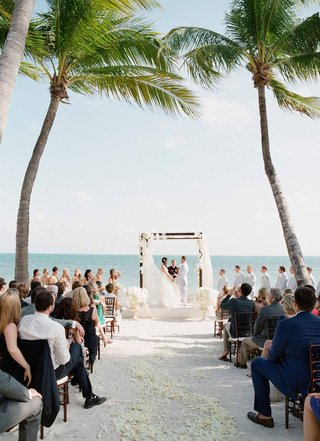 bride-and-groom-at-altar-in-between-two-palm-trees-with-flower-petals-on-sand-and-urns-at-altar