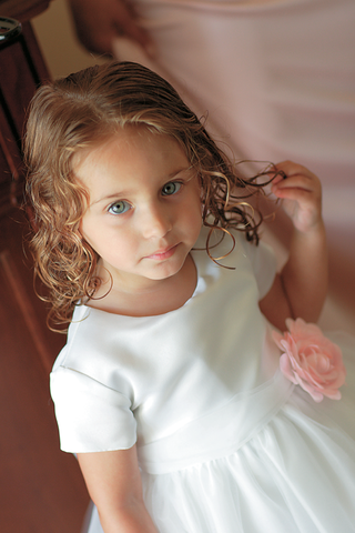 young-flower-girl-with-curls-wearing-white-flower-girl-dress