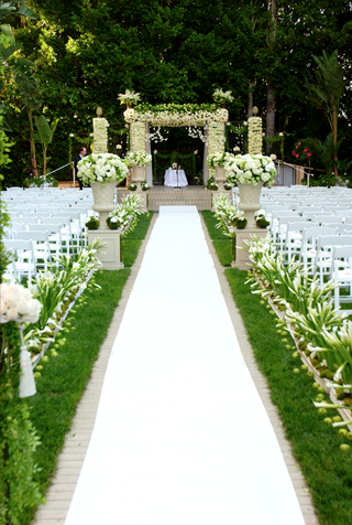 outdoor-ceremony-on-grass-with-white-aisle-runner-and-flowers