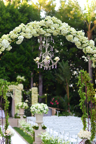 grassy-ceremony-with-hundreds-of-white-flower-arrangements-and-a-chandelier