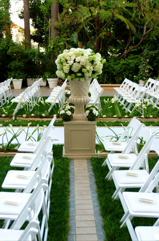white-ceremony-chairs-and-flower-arrangements-along-aisle