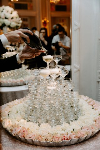 champagne-coupe-glass-tower-white-rose-pink-flowers-on-table-server-pouring-champagne