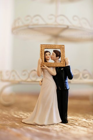 wedding-cake-topper-with-groom-kissing-bride-in-gold-frame
