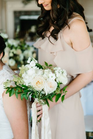 bridesmaid-in-tan-dress-holding-greenery-white-rose-stephanotis-blossom-bouquet