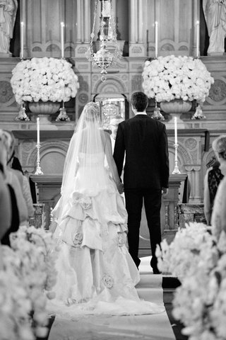 black-and-white-photo-of-bride-and-groom-at-end-of-church-aisle