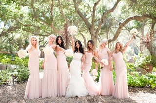 bride-in-vera-wang-and-bridesmaids-in-pink-amsale-dresses-hold-bouquets-in-the-air
