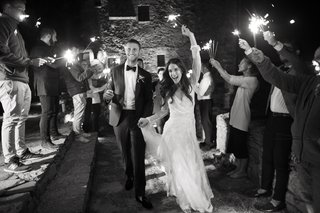 black-white-photo-of-bride-groom-making-grand-exit-from-their-wedding-as-guests-wave-sparklers