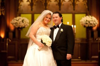 bride-and-groom-smile-at-church-ceremony-altar