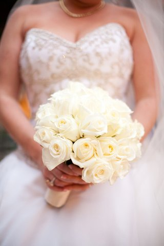 bride-holds-bouquet-with-dozens-of-ivory-roses