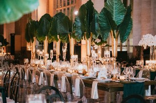 wedding-reception-emerald-green-color-palette-long-table-ghost-chair-with-elephant-ears-orchids