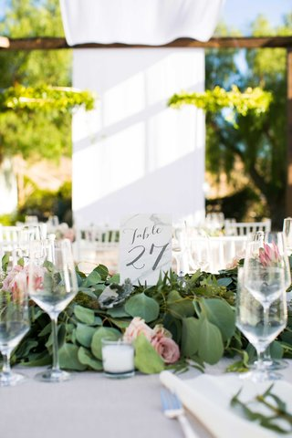 table-number-in-gray-calligraphy-surrounded-by-foliage-with-blush-flowers-on-white-table-linen