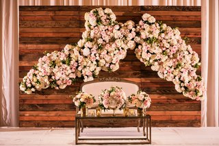 reclaimed-wood-wall-with-flower-wall-decor-sweetheart-table-settee-with-white-pink-flowers