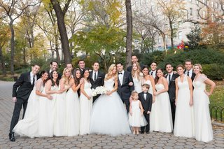 bride-and-groom-with-groomsmen-black-tuxedos-bridesmaids-white-dresses-flower-girl-ring-bearer