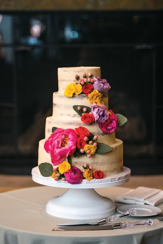 semi-naked-lightly-frosted-small-four-tiered-cake-with-bright-pink-yellow-and-lavender-flowers
