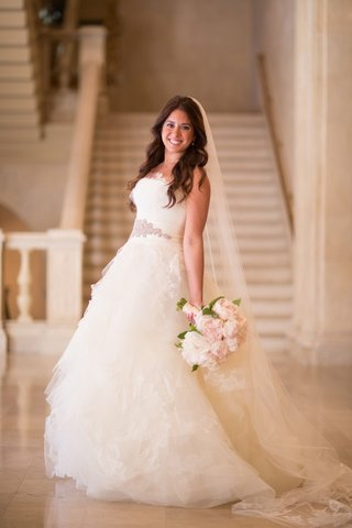 bride-strikes-a-pose-in-a-vera-wang-wedding-dress-with-pink-bouquet