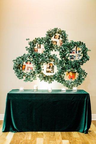 wedding-reception-emerald-green-velvet-linen-eucalyptus-wreaths-with-family-photos-late-loved-ones