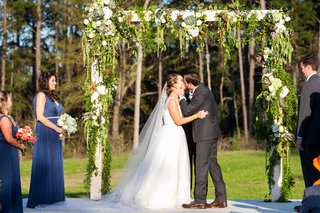 bride-and-groom-first-kiss-at-outdoor-rustic-wedding-ceremony-with-white-arch-and-greenery