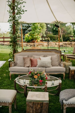 wedding-reception-upholstered-stool-coffee-table-pink-orange-yellow-flowers-settee-sofa-dusty-rose