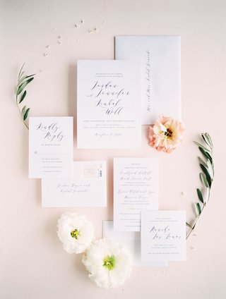 wedding-invitation-suite-detail-shot-with-flowers-pink-white-greenery-flower-petals-stamps-minted