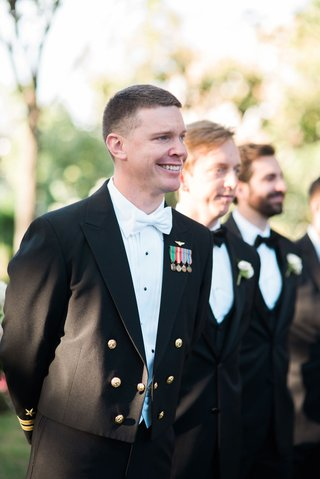 groom-in-white-bow-tie-and-navy-military-uniform-seeing-bride-for-first-time-in-wedding-dress