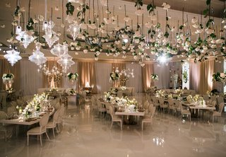 wedding-reception-flowers-hanging-from-ceiling-chandelier-ivory-tables-serpentine-square-round-ivory