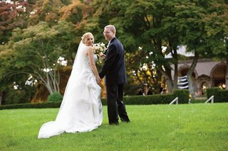 bride-and-groom-look-back-at-camera-in-grass