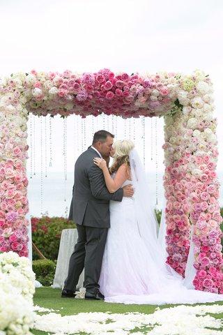 bride-in-pink-ombre-dress-kisses-groom-in-grey-suit
